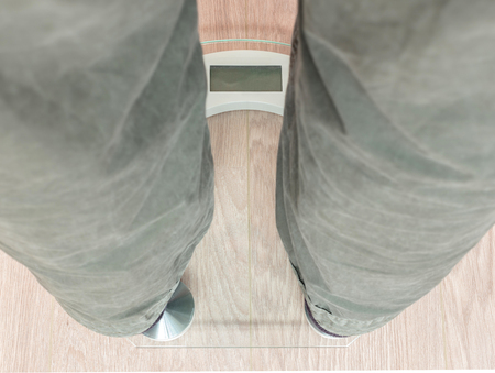 Closeup of mans feet on weight scale -