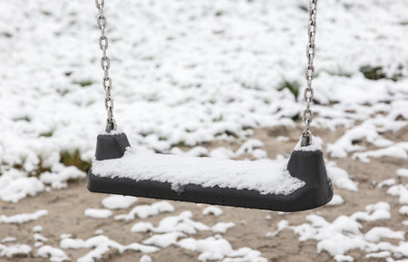 Empty swing in playground - Covered in snow Stock Photo