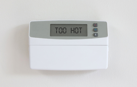 Vintage digital thermostat hanging on a white wall - Covert in dust - Too hot
