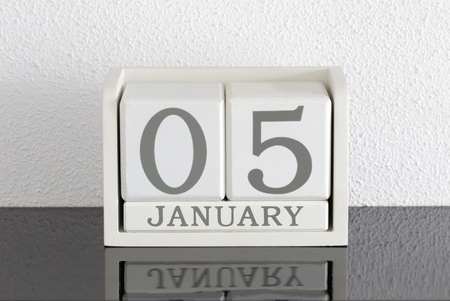 White block calendar present date 5 and month January on white wall background