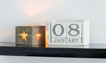 White block calendar present date 8 and month January on white wall background Stock Photo