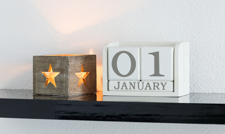 White block calendar present date 1 and month January on white wall background