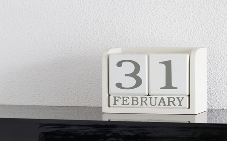 White block calendar present date 31 and month February on white wall background - Extra day Stock Photo