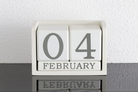 White block calendar present date 4 and month February on white wall background