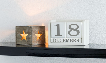 White block calendar present date 18 and month December on white wall background Stock Photo