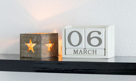 White block calendar present date 6 and month March on white wall background