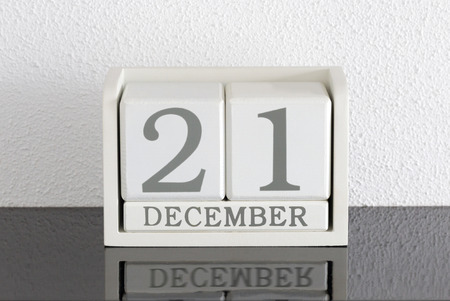 White block calendar present date 21 and month December on white wall background