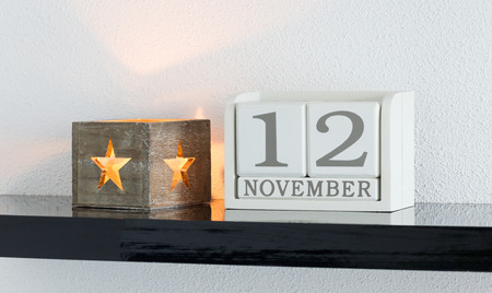 White block calendar present date 12 and month November on white wall background Stock Photo