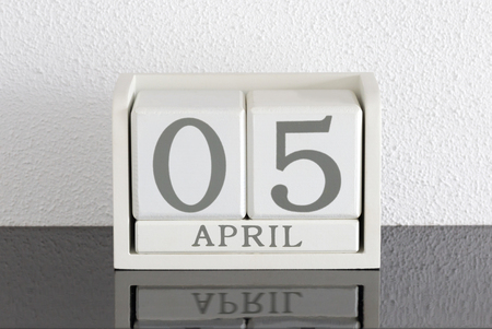 White block calendar present date 5 and month April on white wall background