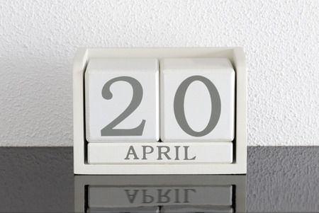 White block calendar present date 20 and month April on white wall background