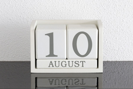 White block calendar present date 10 and month August on white wall background