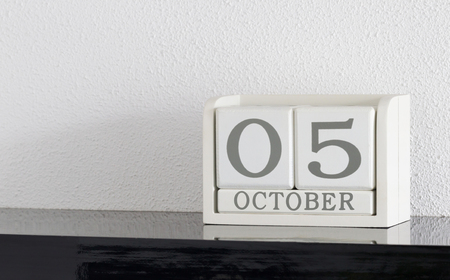 White block calendar present date 5 and month October on white wall background