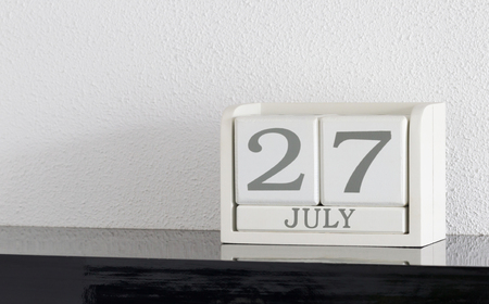 White block calendar present date 27 and month July on white wall background