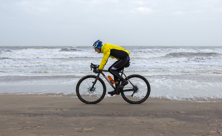 Scheveningen, The Netherlands - 30 December 2017: Cyclist on the beach in Scheveningen, defying a winter storm. Editorial