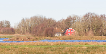 Old dutch house in the typical dutch wet landscape Stock Photo