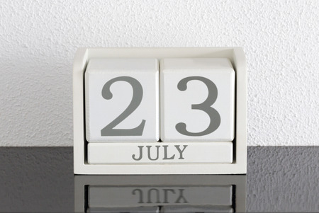 White block calendar present date 23 and month July on white wall background Stock Photo