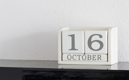 White block calendar present date 16 and month October on white wall background