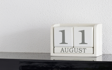 White block calendar present date 11 and month August on white wall background Stock Photo