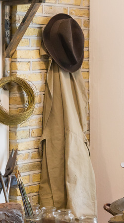 Old hat and coat hanging on a wall Stock Photo