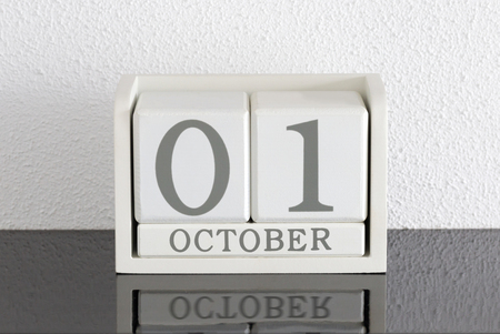 White block calendar present date 1 and month October on white wall background