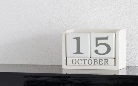 White block calendar present date 15 and month October on white wall background