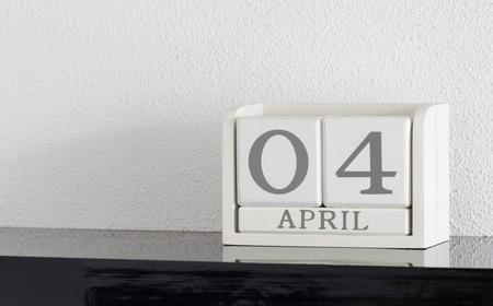 White block calendar present date 4 and month April on white wall background
