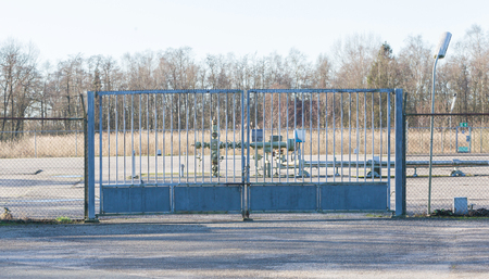 Big metal fence - Entrance to a gas pump - Industry