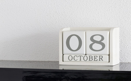 White block calendar present date 8 and month October on white wall background