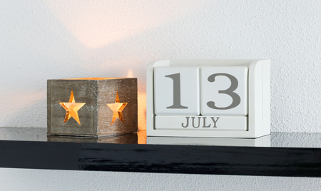 White block calendar present date 13 and month July on white wall background Stock Photo