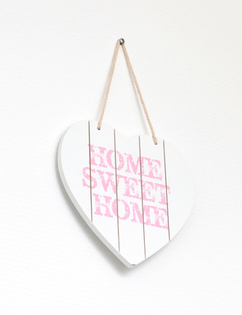 Text home sweet home in a heart-shaped signboard - Hanging on a white wall