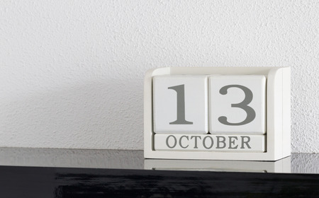 White block calendar present date 13 and month October on white wall background