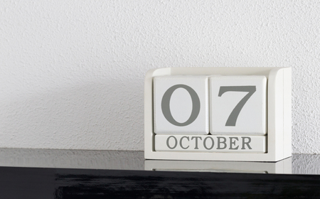 White block calendar present date 7 and month October on white wall background