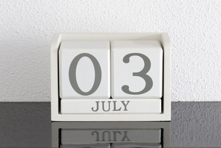 White block calendar present date 3 and month July on white wall background Stock Photo