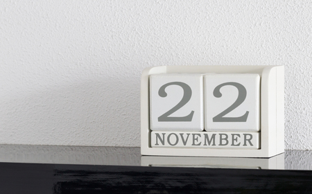 White block calendar present date 22 and month November on white wall background