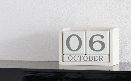 White block calendar present date 6 and month October on white wall background