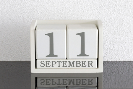 White block calendar present date 11 and month September on white wall background