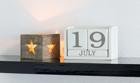 White block calendar present date 19 and month July on white wall background
