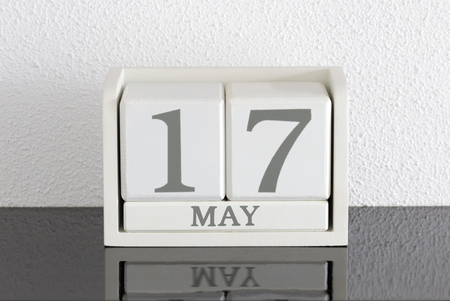 White block calendar present date 17 and month May on white wall background