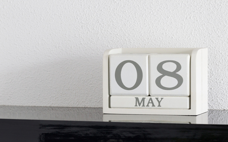 White block calendar present date 8 and month May on white wall background