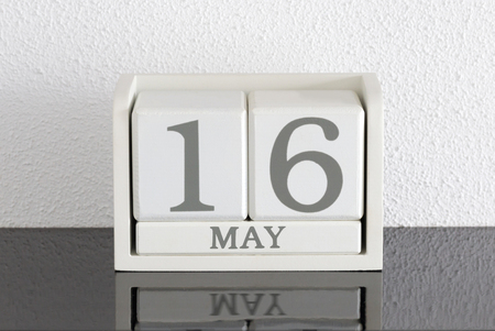 White block calendar present date 16 and month May on white wall background