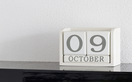 White block calendar present date 9 and month October on white wall background