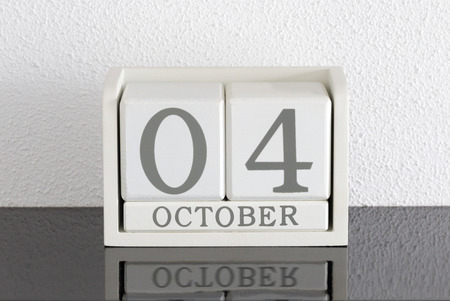 White block calendar present date 4 and month October on white wall background