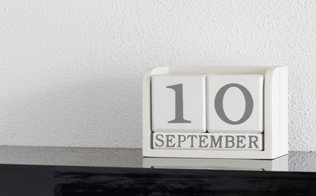 White block calendar present date 10 and month September on white wall background