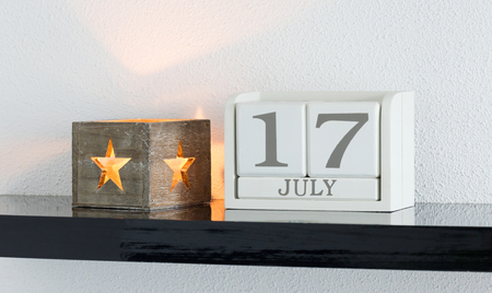 White block calendar present date 17 and month July on white wall background