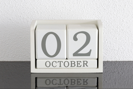 White block calendar present date 3 and month October on white wall background