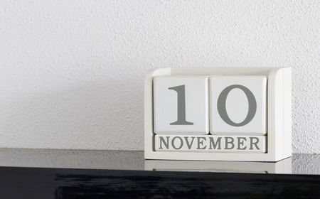 White block calendar present date 10 and month November on white wall background