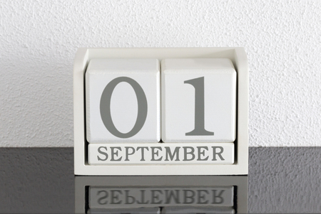 White block calendar present date 1 and month September on white wall background