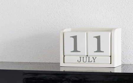 White block calendar present date 11 and month July on white wall background