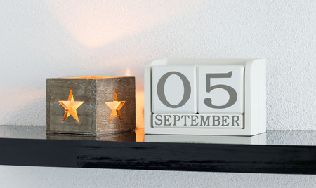 White block calendar present date 5 and month September on white wall background Stock Photo