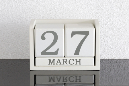 White block calendar present date 27 and month March on white wall background